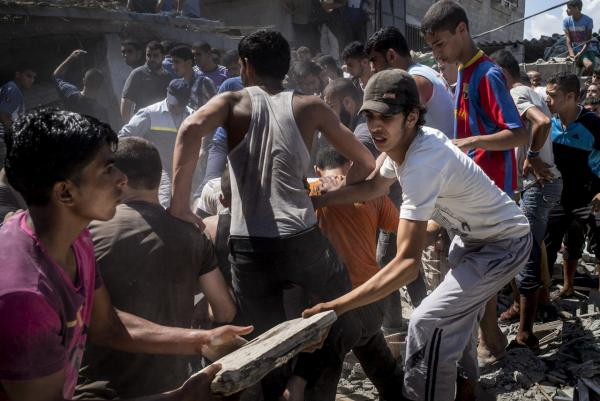 Palestinian men gather remove the rubble of a house hit by an Israeli airstrike in the al-Shati refugee camp in Gaza City on August 4, 2014, trying to look for survivors. (Marco Longari/AFP/Getty Images)