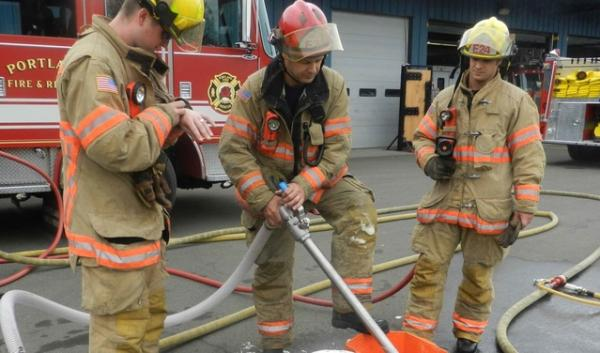 Firefighters with Portland Fire and Rescue demonstrate how they would apply fire retardant foam to contain and extinguish an oil train fire.