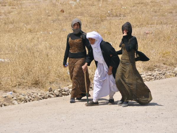 A displaced family from the minority Yazidi sect flees the violence in Sinjar, Iraq, west of Mosul, on Tuesday. Tens of thousands fled the weekend assault on Sinjar and are now surrounded, according to witnesses and the United Nations.