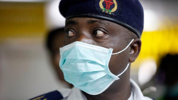 A Nigerian health official screens passengers for signs of Ebola at the Murtala Muhammed International Airport in Lagos on Monday.