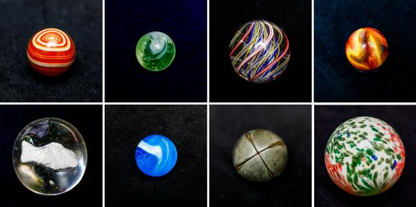 Marbles from the collection of Doug Watson. Top row from left: hand-cut agate, green slag, handmade German latticino, champion furnace swirl. Bottom row: German handmade flame-polished sulphide, aqua slag, hollow steelie, handmade flame-polished German onionskin.