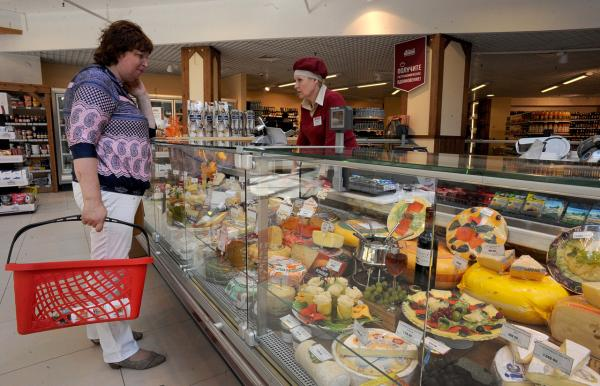 A Russian customer buys cheese in Saint Petersburg on August 7. Russia retaliated against tough new Western sanctions, banning most food imports from the United States and the European Union and threatening to block flights over its airspace. (Olga Maltseva/AFP/Getty Images)