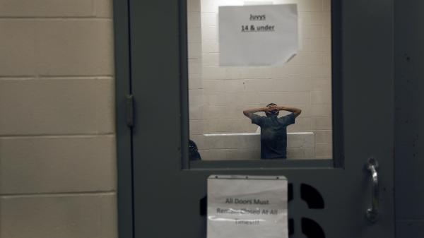 A young immigrant caught crossing the border illegally is housed inside the McAllen Border Patrol Station in McAllen, Texas, last month.