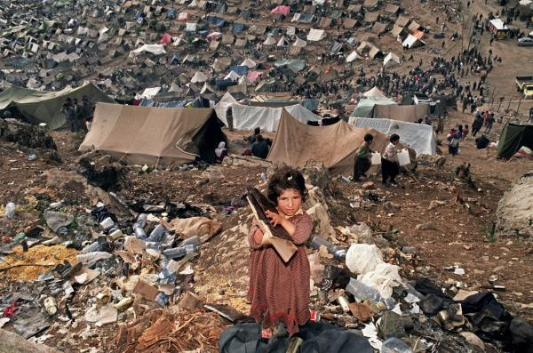 A young Kurdish girl holds U.S. Army rations in 1991. The tents of the Cukurca refugee camp on the Turkish side of the Iraqi border are in the background. The U.S. led the effort to assist a half-million Kurds in the aftermath of the 1991 Gulf War.