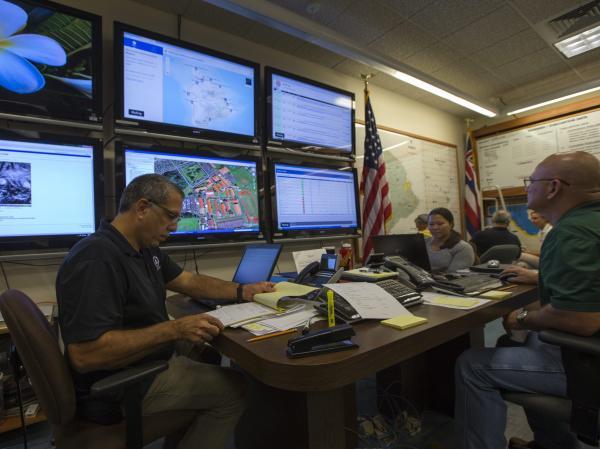 Hawaii County Civil Defense Administrator Darryl Olivera (left) reviews storm data in Hilo, Hawaii.