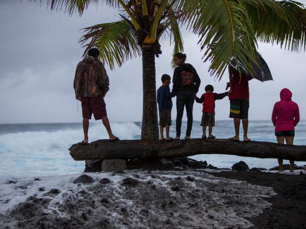 A large wave generated by the storm sends whitewater high up the shoreline Thursday, surprising spectators in Pohoiki.