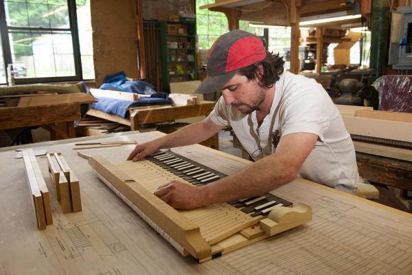 Will Plouffe, a harpsichord builder with Zuckermann Harpsichords International, levels and balances a keyboard he built. (Shana Sureck/WNPR)