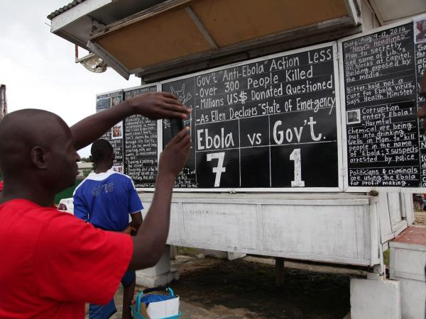 Liberians read the Daily Talk chalk board on the Ebola outbreak in the capital, Monrovia, on Saturday. According to statistics from the World Health Organization, 959 patients have died from Ebola in West Africa.