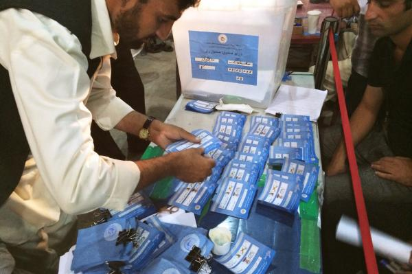 An Afghan election worker examines ballots to check for similar handwritten marks that would suggest ballot-stuffing fraud.