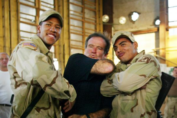 U.S. Army soldiers gets their photo taken with Williams during his 2002 visit to the Bagram military base in Afghanistan.