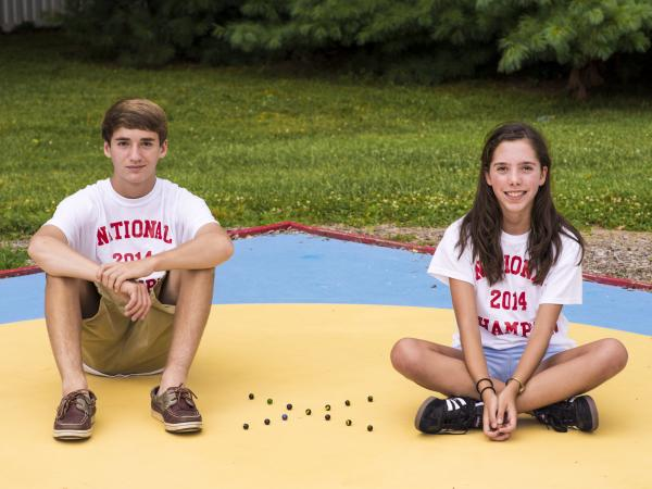 Dominic Rudakevych and Marilyn Fisher, 2014 champions of the National Marbles Championships in Wildwood, N.J., pose at the marbles rings in Middletown, Md. The two 13-year-olds train with the Frederick County Knucklers, a competitive marbles recreational program in Maryland.