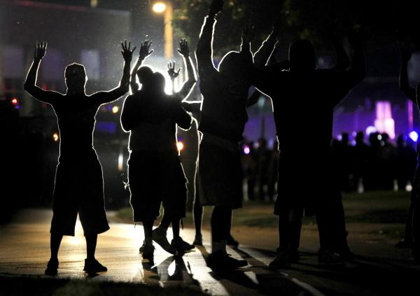 People raise their hands in the middle of the street as police wearing riot gear move toward their position trying to get them to disperse in Ferguson, Mo. The city has been in turmoil after an unarmed black teenager, Michael Brown, was gunned down by police last week.