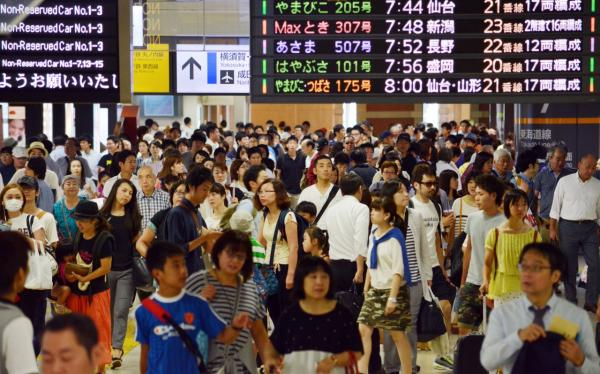 Travelers and commuters walk on the concourse of JR Tokyo Station, in Tokyo on August 13, 2014. Japan's economy shrank in the latest quarter as a sales tax hike slammed the brakes on spending by the nation's households and companies, the first significant pullback since late 2012, government data showed on August 13. (Kashuhiro Nogi/AFP/Getty Images)