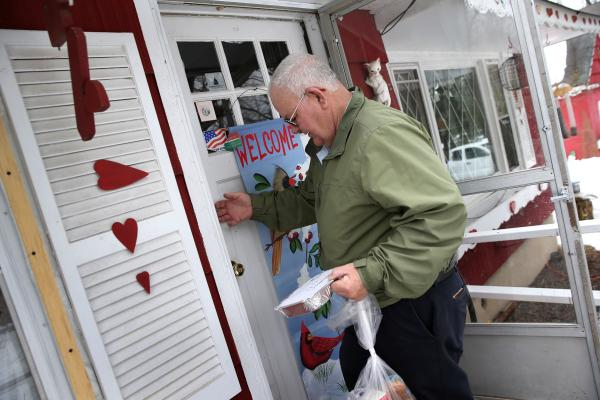 Tom Neville of Catholic Services knocks before entering with a Meals on Wheels delivery to an elderly widow on March 12, in Hainesville, N.J.