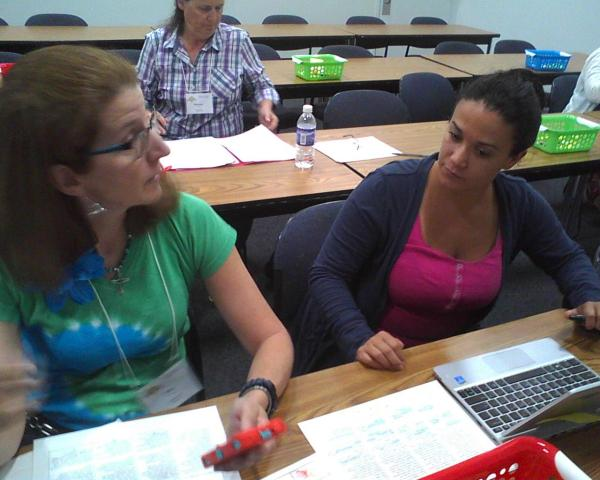 Lisa Yim, a Montgomery County teacher (left) and Baltimore County teacher Sarah Clark (right) discuss ways to implement a Common Core reading concept during a training session at the Universities of Shady Grove in Rockville.