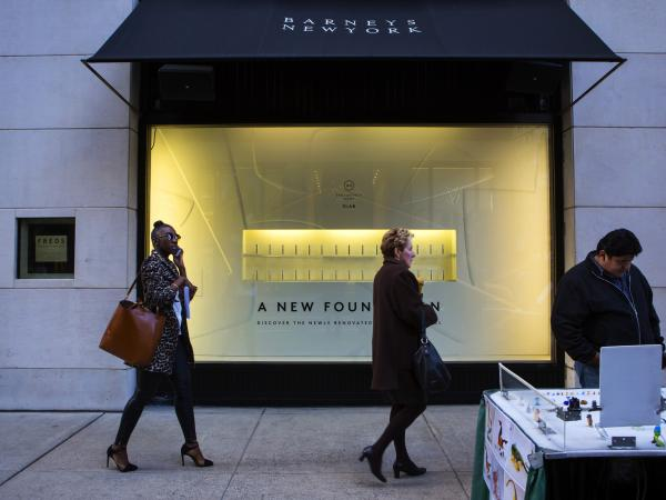 People walk by a Barneys New York retail store in New York City.
