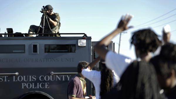 A member of the St. Louis County Police Department points his weapon in the direction of a group of protesters in Ferguson.