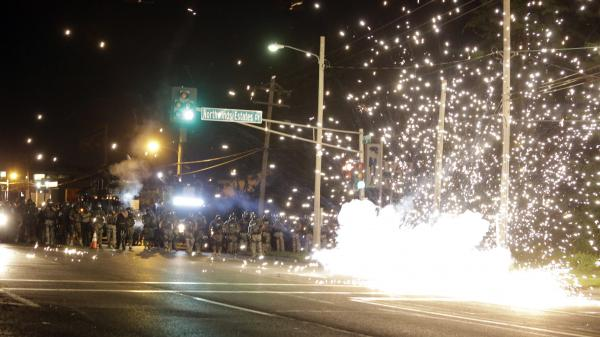 A device deployed by police goes off in the street as police and protesters clash in Ferguson, Mo., Wednesday. Protests have rocked the St. Louis suburb since a police officer shot an unarmed black teenager Saturday.