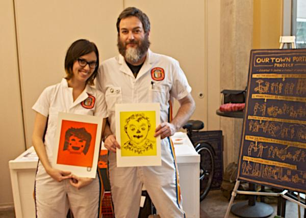 Bryce McCloud (right) and his assistant Elizabeth Williams, who run a mobile self-portrait project called Our Town in Nashville, TN,  pose with their own portraits. (Nina Cardona/WPLN)
