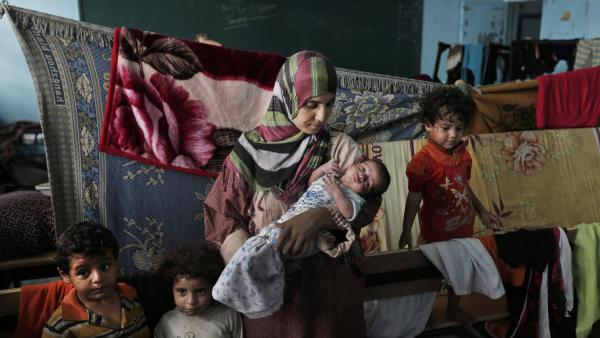 Displaced Palestinian Emada al-Attar, 23, holds her 16-day-old baby boy Anous on Aug. 8 in a classroom where they sleep in a United Nations school in Gaza City. Thousands of Palestinians lost their homes in the recent fighting and are still taking refuge in schools. It's not clear when the schools will reopen.