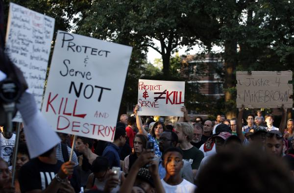 Protestors hold signs in support of those in Ferguson, Mo., during a rally at Meridian Hill Park, also known as Malcolm X Park, in Washington.