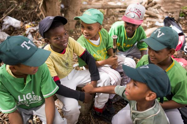 Anderson Desir (second from left) jokes with his teammates at a baseball diamond in San Pedro de Macoris, Dominican Republic. Anderson was born in Haiti, and he and his family are among those who can apply to regularize their status under the new laws.