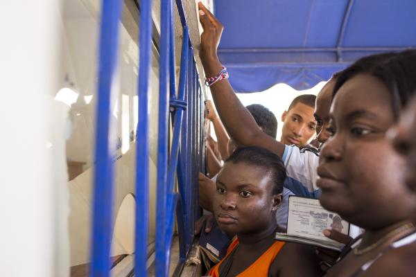 "A crowd presses up to a document processing window at the Palace of Justice in San Pedro de Macoris. Many of those waiting in line are Haitian nationals requesting background checks, one of the steps required to ""regularize"" their status in the Dominican Republic."