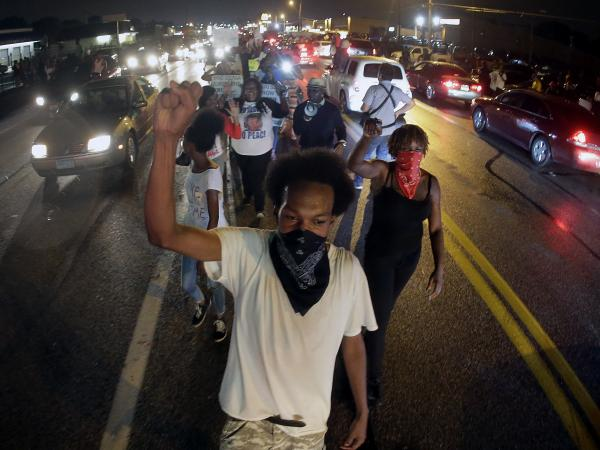 Protesters march Friday in front of a convenience store that was looted and burned following the shooting death of Michael Brown by police nearly a week ago in Ferguson, Mo.