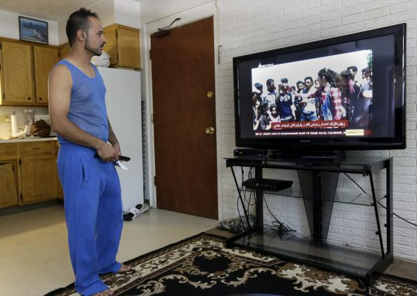 Lincoln, Neb., is home to a sizable community of Iraqi Yazidis — including Ismaeil Khalaf, shown here in his home watching the latest news about the Yazidi crisis in Iraq. Lincoln Yazidis petitioned for U.S. intervention to prevent the genocide of their friends and family.