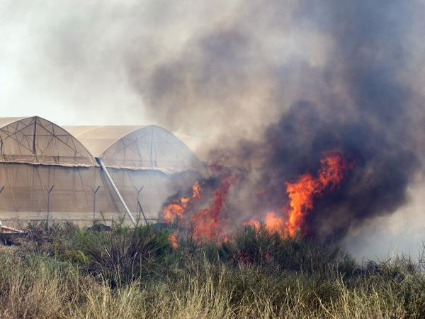 Fire consumes a field close to greenhouses on a farm in the Israeli Mediterranean coastal city of Ashkelon after a rocket fired by Palestinian militants from the Gaza Strip landed there.