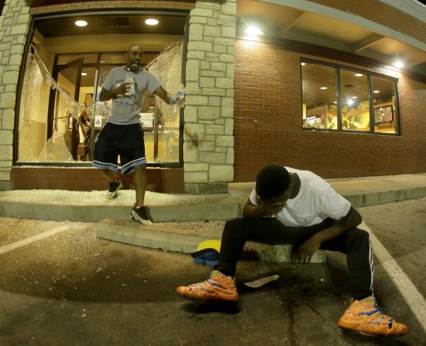 A man tries to recover from tear gas as people leave a McDonald's restaurant Sunday during a protest for Michael Brown in Ferguson, Mo. After police fired tear gas, people used bottles of water and milk to try to clear their eyes.