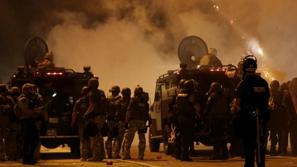 Police wait to advance after tear gas was used to disperse a crowd Sunday during a protest for Michael Brown, who was killed by a police officer last Saturday in Ferguson, Mo.