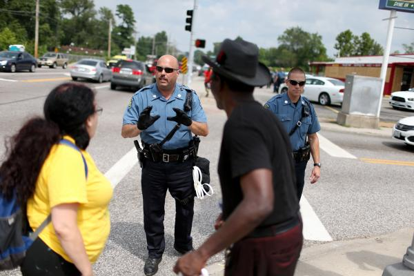 Police officers advise demonstrators that they can't stop walking as they protest.