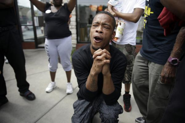 A man prays as police try to disperse a small group of protesters. In his press conference Monday, Obama said he wanted to ensure that justice was carried out fairly in Ferguson.