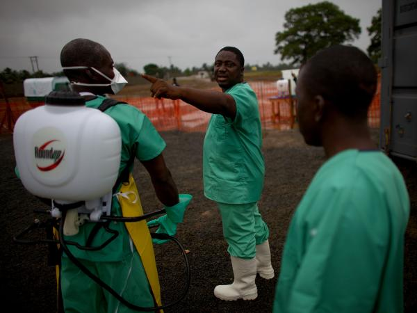Protected by layers of gear, health care workers prepare to enter the isolation ward of the new Ebola treatment facility.