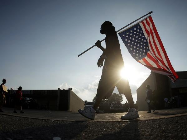 Demonstrator Duane Merrells walks with an upside down flag in Ferguson, Mo., on Monday. The killing of the unarmed black teen sparked a week of protests.