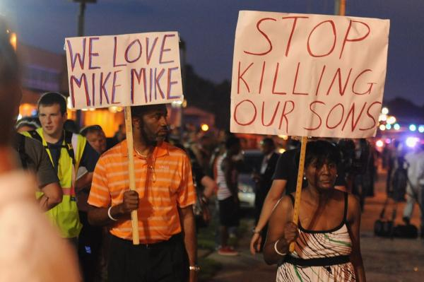 Demonstrators display signs during a protest on West Florissant Avenue in Ferguson, Missouri on August 18, 2014. Police fired tear gas in another night of unrest in a Missouri town where a white police officer shot and killed an unarmed black teenager. (Michael B. Thomas/AFP/Getty Images)