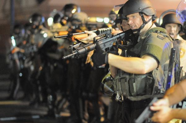 Law enforcement officers watch on during a protest on West Florissant Avenue in Ferguson, Missouri on August 18, 2014. Police fired tear gas in another night of unrest in a Missouri town where a white police officer shot and killed an unarmed black teenager. (Michael B. Thomas/AFP/Getty Images)