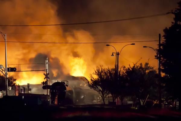 Firefighters douse blazes after a freight train loaded with oil derailed in Lac-Megantic in Canada's Quebec province on July 6, 2013, sparking explosions that engulfed about 30 buildings in fire. (François Laplante-Delagrave/AFP/Getty Images)