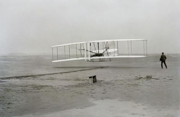 First flight of the Wright Flyer I, December 17, 1903, Orville piloting, Wilbur running at wingtip. (John T. Daniels/Wikimedia Commons)