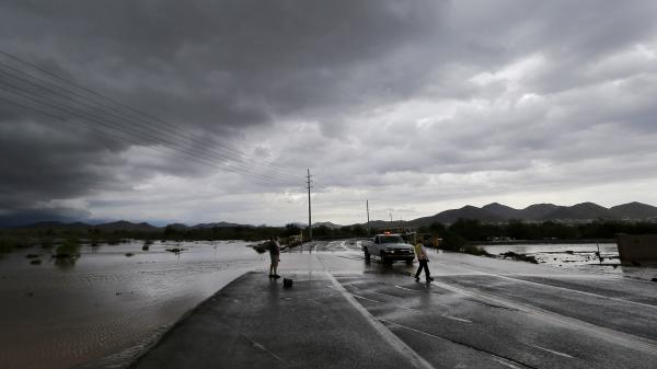A Phoenix official blocks a closed section of road as flash-flood waters overrun Skunk Creek through the Sonoran Desert on Tuesday.