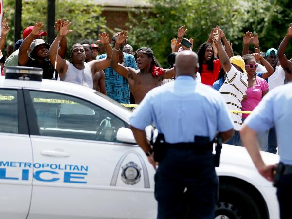 "People raise their arms while chanting, ""Hands up. Don't shoot,"" near where St. Louis police say officers shot and killed a 23-year-old man who was wielding a knife and refused to drop it on Tuesday."