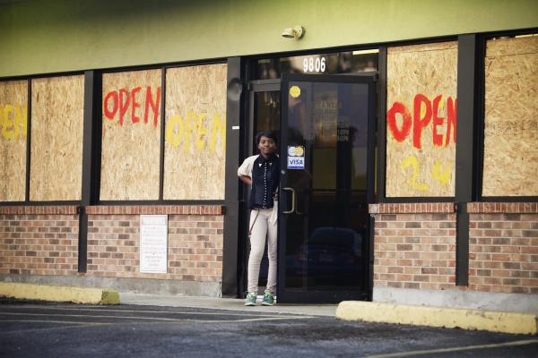 A woman stands before a restaurant on West Florissant Avenue where rioting took place earlier this week. Most of the stores on this stretch are boarded up — some after they were damaged by looters, and some as a precaution — even as many remain open for business.
