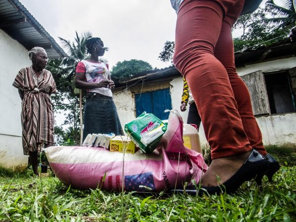 An ActionAid worker delivers basic goods to Amanda Ellis, whose mango business has crashed since five members of her family died of Ebola. She says that she has been abandoned by her friends.