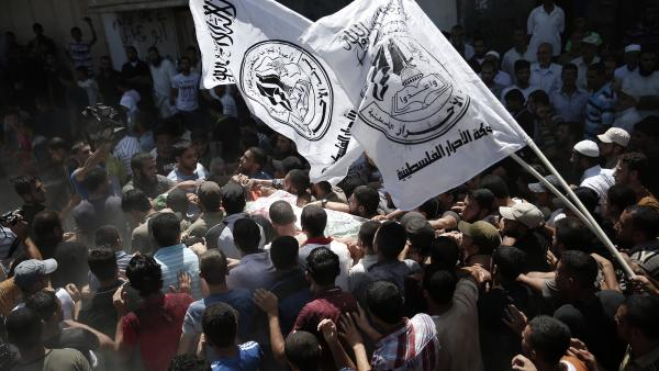 Hamas supporters carry the body of one of three Hamas senior commanders killed Thursday by an airstrike in the Gaza Strip.
