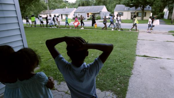 Children watch from their home in Ferguson, Mo., on Wednesday as people march to the police station to protest the shooting of Michael Brown. The school year was delayed in the St. Louis suburb amid protests, riots and looting in the wake of the police shooting. But classes are expected to start Monday.