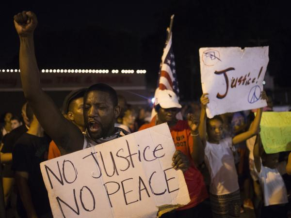 Demonstrators protest the killing of unarmed 18-year-old Michael Brown across the street from the Ferguson Police Department in Ferguson, Mo., Friday night. More than a week of unrest has largely given way to peaceful protests recently.