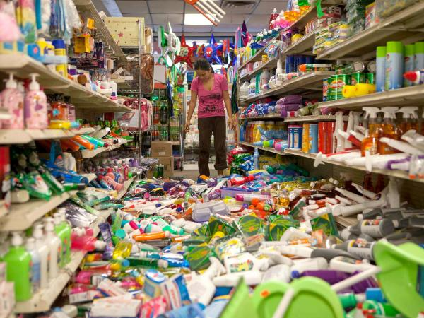 Nina Quidit cleans up the Dollar Plus and Party Supplies Store in American Canyon Calif. after the quake on Sunday.