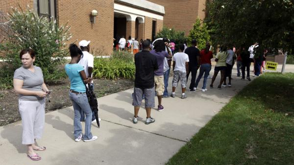 People line up to take part in an amnesty program to clear up outstanding misdemeanor arrest warrants in August 2013, in Ferguson, Mo. For those living on the economic margins, the consequences of even a minor criminal violation can lead to a spiral of debt, unpaid obligations, unemployment and even arrest.