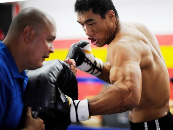 Taishan Dong works with coach John Bray at the Glendale Fighting Club, north of Los Angeles. At 6 feet 11 inches tall, Taishan towers over opponents.